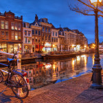 Night scene in Leiden, The Netherlands with old houses along the Nieuwe Rijn Canal.