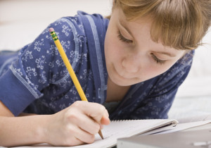 young girl writing on a pad